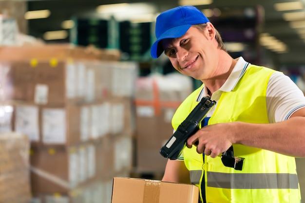 Warehouseman com colete de proteção e scanner, verifica o código de barras do pacote, ele está no armazém da empresa de expedição de mercadorias
