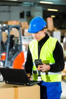 Warehouseman com colete de proteção, scanner e laptop em armazém na empresa de agenciamento de cargas