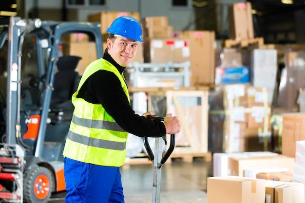 Warehouseman em colete de proteção puxa um motor com pacotes e caixas no armazém da empresa de encaminhamento de frete - uma empilhadeira é em segundo plano