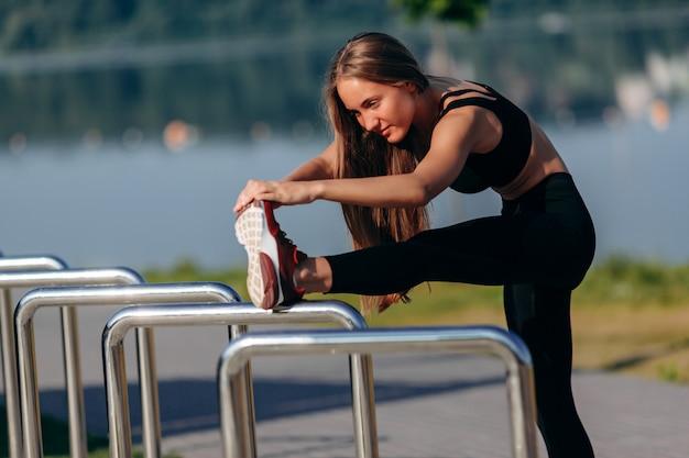 Warmimg desportivo menina ao ar livre e alongamento