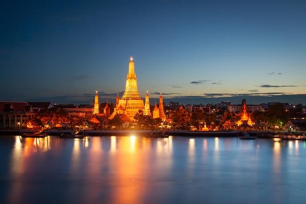 Wat arun através do rio chao phraya durante o pôr do sol em bangkok, tailândia