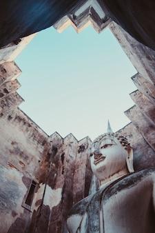 Wat tra phang thong lang enorme monumento de escultura de buda ao deus budista pregando com ofertas. escultura de pedra branca dentro da parede da mandapa. parque histórico de sukhothai.