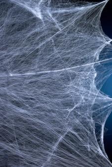 Web branca esticada com luz de fundo azul, plano de fundo para o feriado halloween