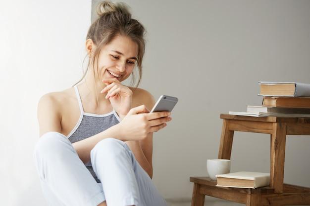 Web surfando da mulher adolescente bonita nova que olha a tela do telefone que sorri sentado no assoalho entre livros velhos perto da janela sobre a parede branca.