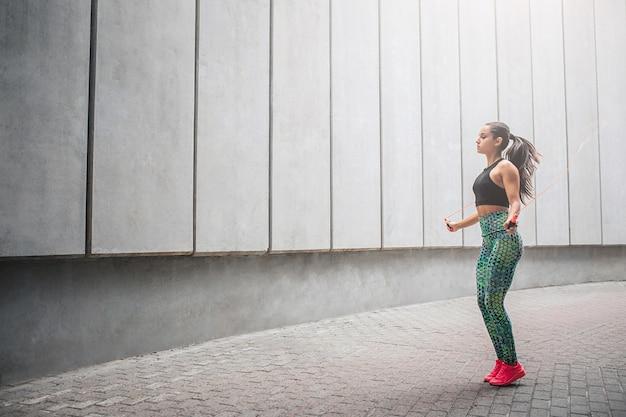 Wel-shaped jovem mulher pulando com corda sozinha no corredor