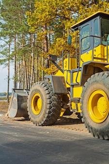 Wheelloader na floresta perto da borda da vista traseira da estrada