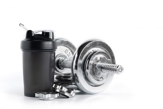 Whey proteína shaker garrafa com haltere de placa de cromo isolado no fundo branco, equipamentos de fitness