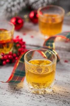 Whisky, brandy ou licor shot e decorações de natal em fundo branco de madeira. conceito de férias sazonais.
