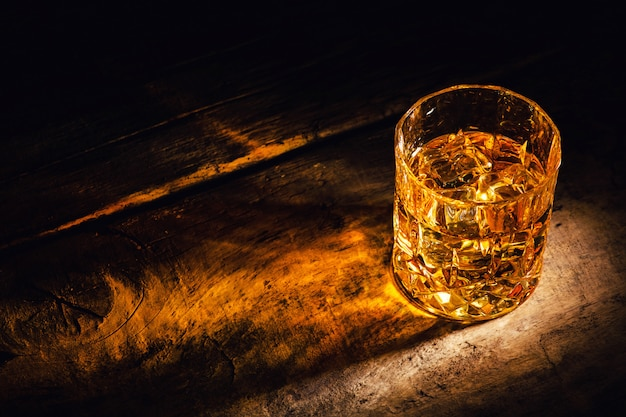 Whisky com cubos de gelo em fundo de madeira