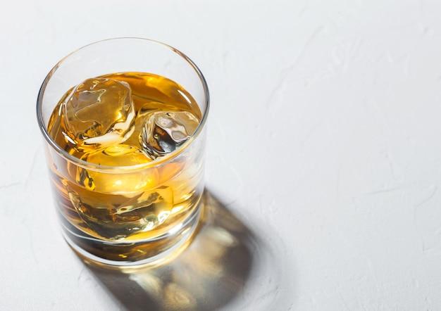 Whisky de single malte em copo com cubos de gelo com sombra no fundo branco