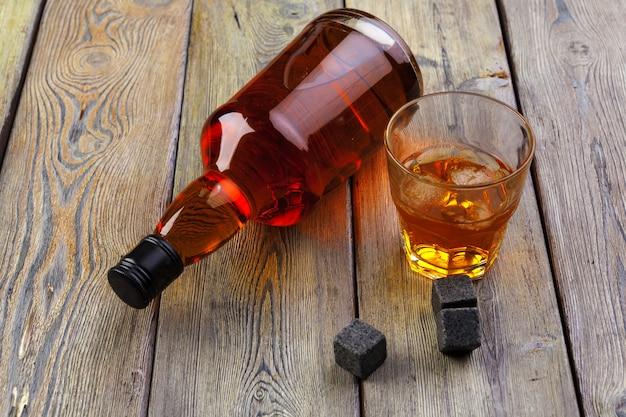Whisky e pedras de uísque em uma mesa de madeira