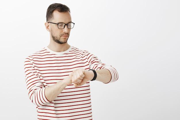 Wiast-up shot de um empresário ocupado e focado de óculos, olhando relógios digitais, verificando a hora enquanto espera pelo parceiro de negócios