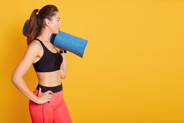 Wiev lateral da jovem mulher caucasiana bonita em pé e segurando o tapete de ioga azul por cima do ombro, estando pronto para o exercício no ginásio