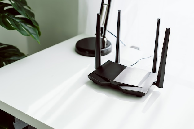 Wifi e roteador de banda larga na mesa branca na sala em casa.