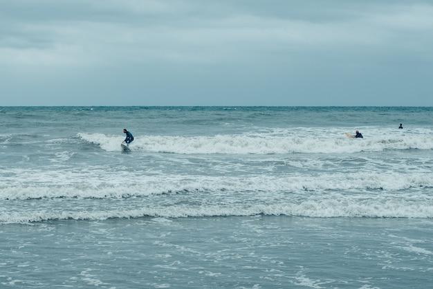 Windsurfistas tentando montar pequenas ondas durante uma tempestade.