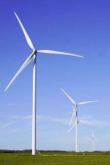 Windwheels voando energia eólica acima grande turbina eólica em campo em dia de sol