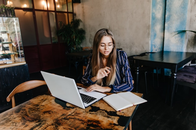 Winsome secretária feminina trabalhando com computador. foto interna de uma linda estudante caucasiana usando o laptop para fazer o dever de casa.