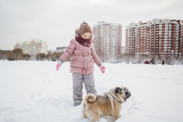 Winter e uma garota com seu cachorro, neve e jogos na neve, passeando com um animal de estimação, comunicando-se com animais