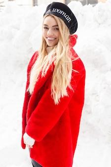 Winter, fashion, people concept - fashion retrato de uma bela jovem caminha pela cidade sorrindo, casaco de pele vermelha, close-up, flocos de neve, inverno frio, respirar ar fresco no dia de inverno geada. pôr do sol