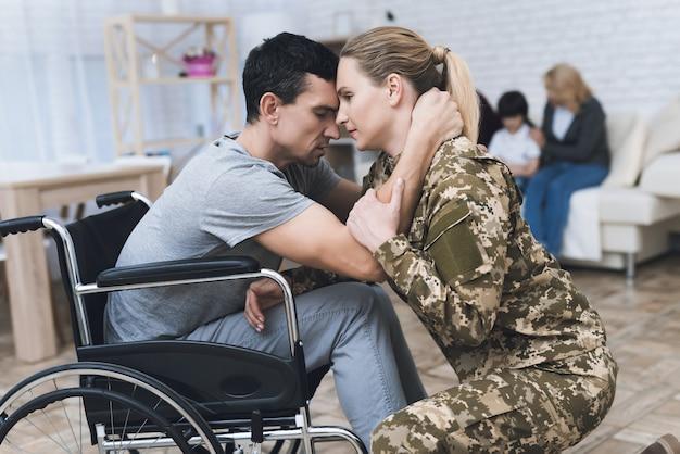 Wman vai para o serviço militar. ela se despede da família.