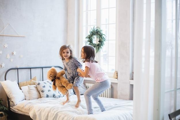Wo meninas, irmãs lutando travesseiros na cama, a janela decorada com uma guirlanda de natal, vida, infância