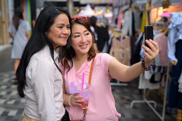 Wo mulheres asiáticas maduras, compras juntas no mercado de rua
