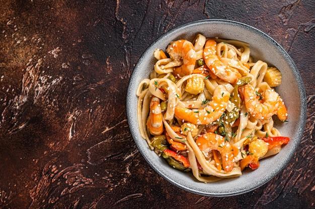 Wok chinês frito macarrão udon com frutos do mar e camarão camarão em uma tigela. fundo preto. vista do topo. copie o espaço.