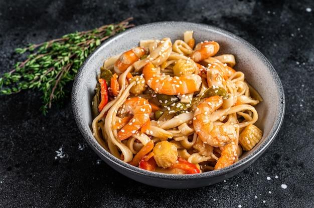 Wok chinês frito macarrão udon com frutos do mar e camarão camarão em uma tigela. fundo preto. vista do topo.
