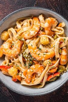 Wok chinês frito macarrão udon de frutos do mar e camarões em uma tigela. preto