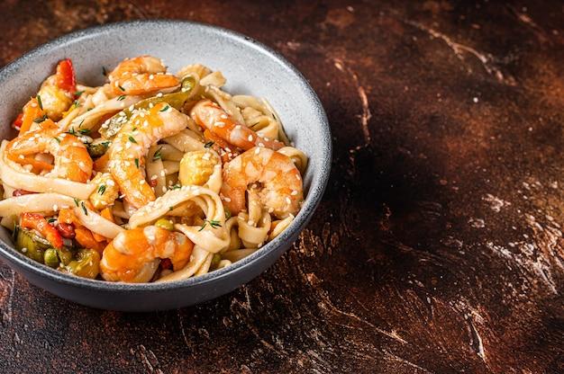 Wok chinês macarrão udon de frutos do mar frito com camarão camarão em uma tigela