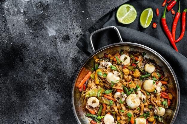 Wok com frite macarrão udon, choco e legumes. superfície preta. vista do topo. copie o espaço