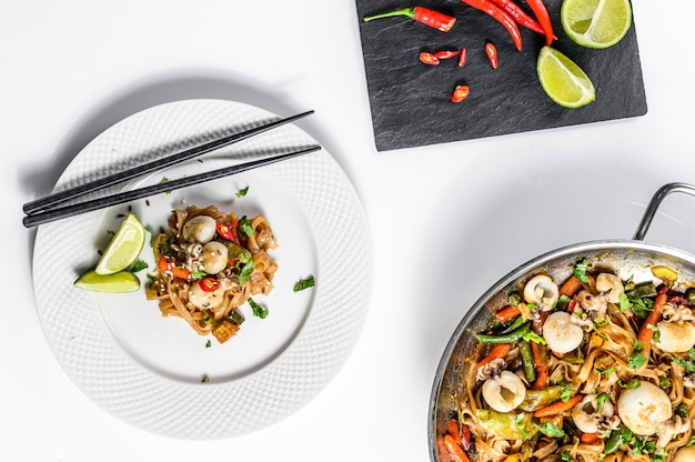 Wok com frite macarrão udon, frutos do mar e legumes. fundo branco. vista do topo