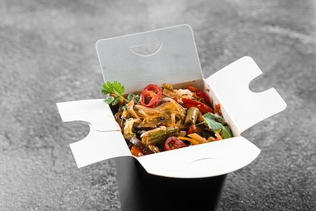 Wok em caixa de macarrão de arroz em recipiente preto para comida