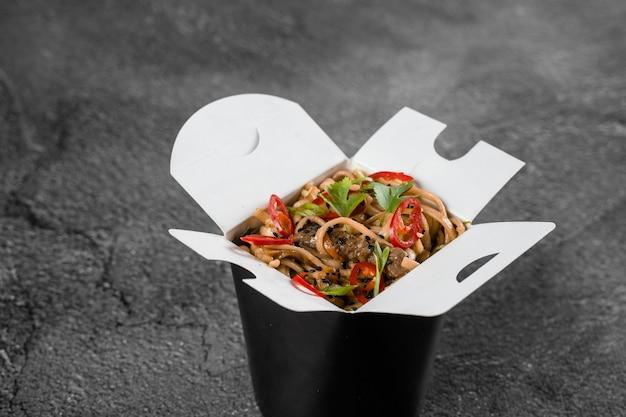Wok em caixa de macarrão picante em recipiente de comida preta