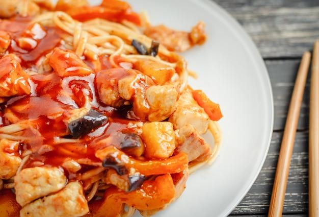 Wok macarrão udon com frango e legumes em um prato branco, close-up