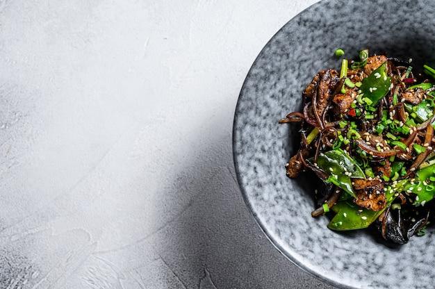 Wok. soba frite macarrão com carne e legumes. fundo cinza. vista do topo. copie o espaço