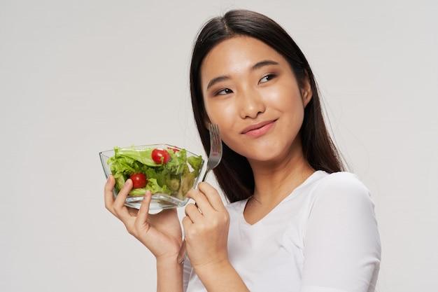 Woma asiático comendo uma salada