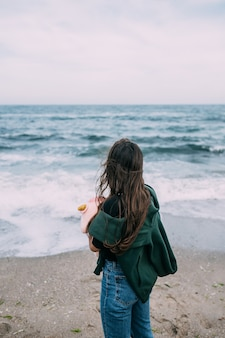 Woma fotografa em um smartphone as ondas do mar