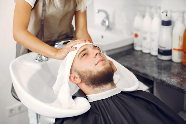 Woma lavando a cabeça do homem em uma barbearia