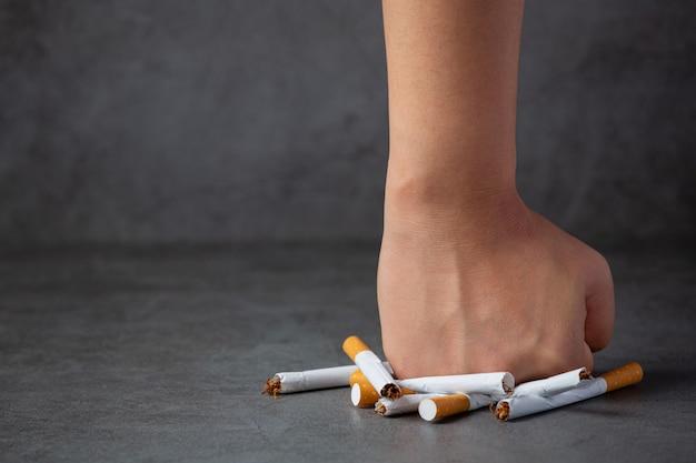 Womanan mão segurando e destruir cigarros na superfície escura. conceito de dia de mundo sem tabaco.