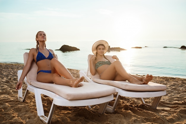 Womans linda em trajes de banho tomando banho de sol, deitado nas espreguiçadeiras perto do mar