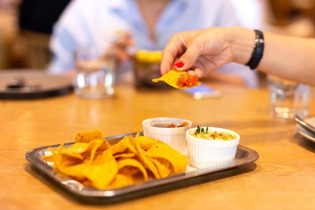 Womans, mão, com, vermelho, cor, prego, tendo, um, tortilla chip, bruschetta, molho, em, tempo almoço, com
