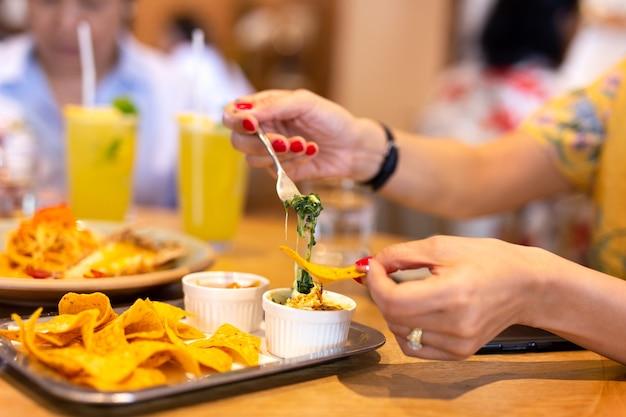 Womans, mão, com, vermelho, cor, prego, tendo, um, tortilla, lasca, com, espinafre, nacho, queijo, molho, sagacidade