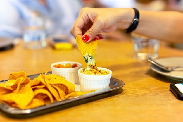 Womans, mão, com, vermelho cor, prego, tendo, um, tortilla lasca, com, nacho, molho queijo, em, almoço, ti
