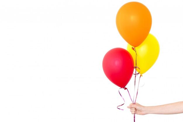 Womans mão segura balões em um fundo branco