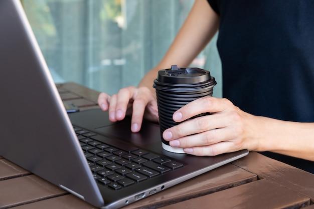 Womans mãos com copo de papel de café ou chá e laptop no café ou terraço de casa