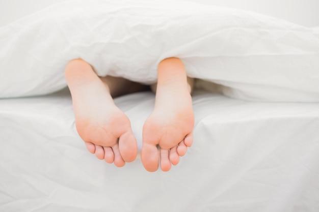 Womans pés saindo do cobertor