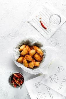Wontons fritos, malagueta seca, guardanapos de papel