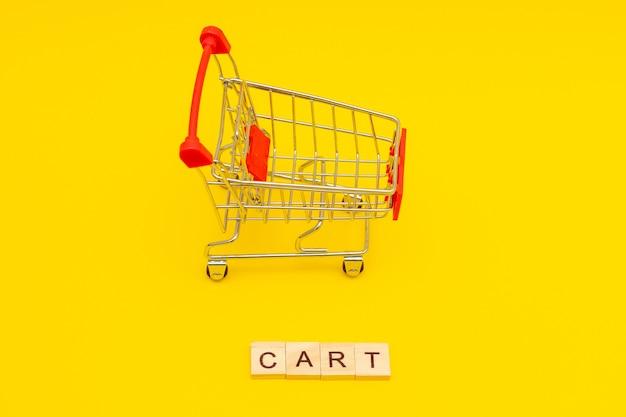 Word cart feito de cubos de madeira em fundo amarelo com carrinho de compras de brinquedos