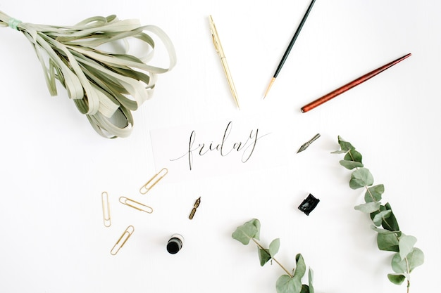 Word friday escrita com caligrafia em branco com caneta, pincel, eucalipto e clipes